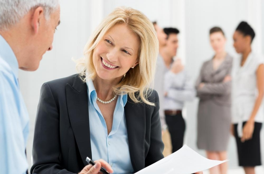 woman-in-suit-smiling-at-older-man-near-other-employees-1-412572-edited.jpg