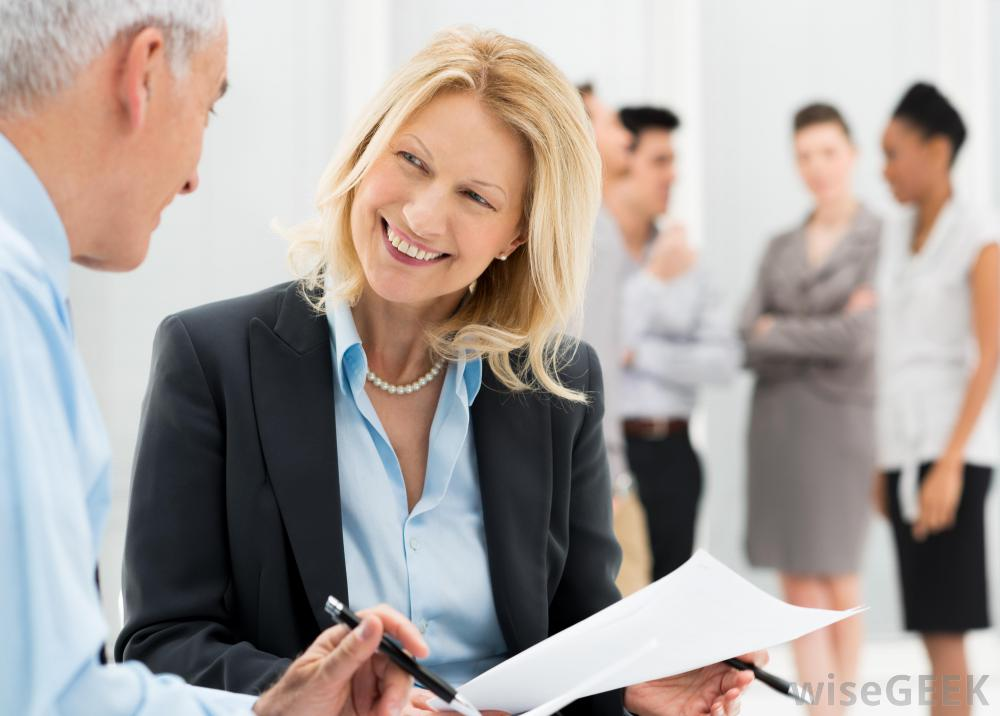 woman-in-suit-smiling-at-older-man-near-other-employees